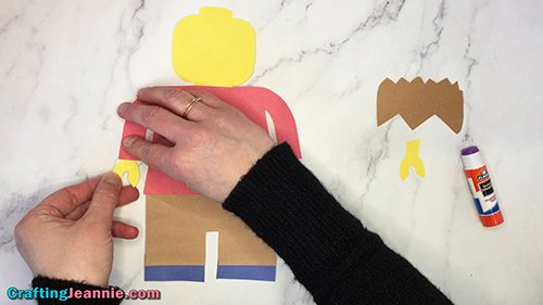 gluing on the hand of the paper minifigure