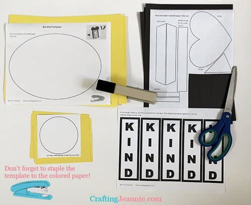 Stapling the bee craft template to colored paper