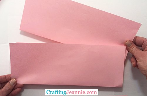 pink paper folded and stacked ready to be cut