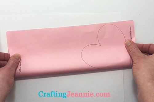 hands folding heart popsicle stick template in half