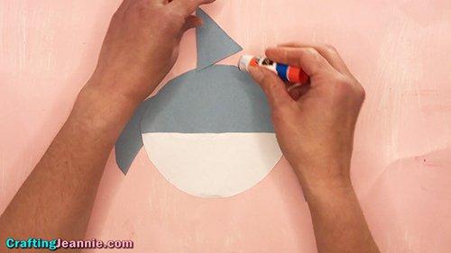 gluing on the preschool shark craft fin