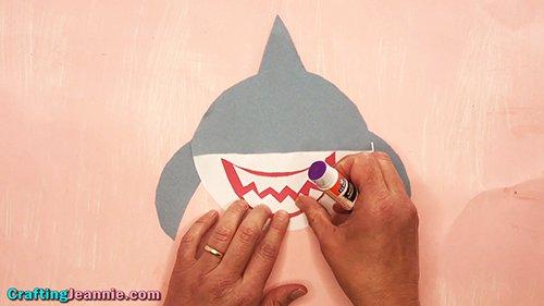 gluing on the paper shark craft teeth