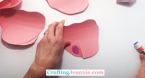 add glue to the bottom of the rose petal