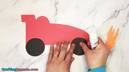 gluing on wheels to paper race car