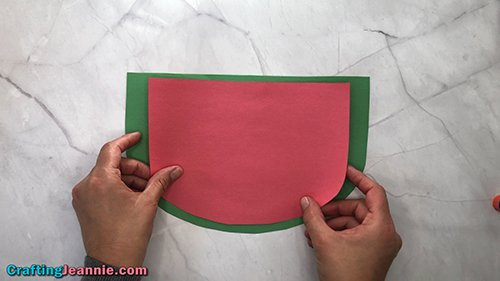 glue the red paper to the green paperof the preschool Watermelon craft