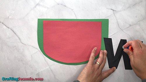 add glue to the black W of the preschool Watermelon craft