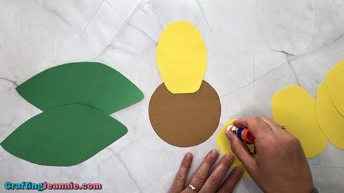 glue petals onto sunflower craft for kids