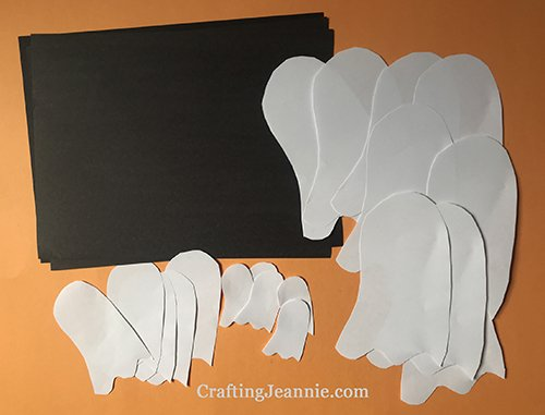 halloween ghost craft pieces. Three different sized white ghosts and black paper