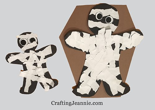 Paper Halloween Mummy. black person outline with white paper strips glued on.
