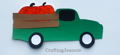 green truck with pumpkins in the bed