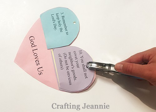punching holes into ten commandments heart craft after assembly