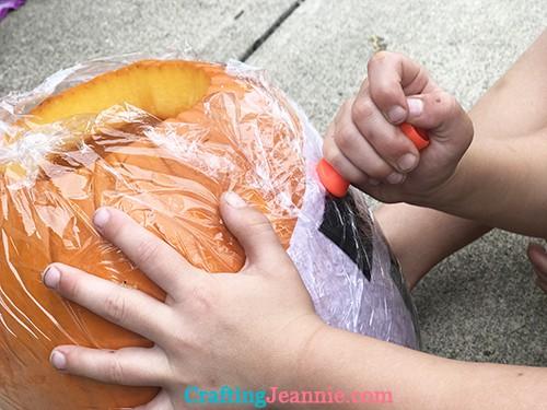 carve pumpkin through plastic wrap