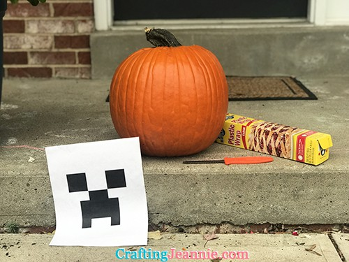 pumpkin, plastic wrap, knife, and printout for carving