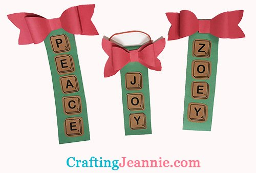 paper scrabble ornaments that say peace, joy and zoey