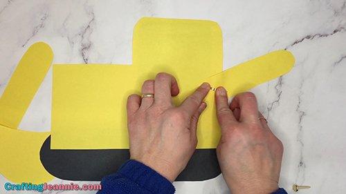 back of excavator and hands bending brass fastener