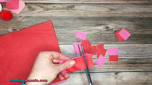 cutting out lots of red and pink tissue paper squares