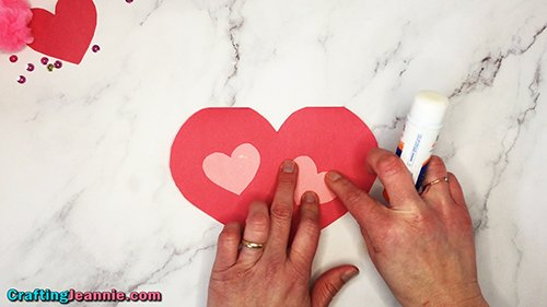 gluing pink hearts onto the front of the card