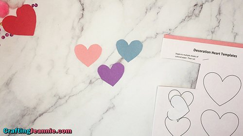 three small hearts cut out for decorating the cards