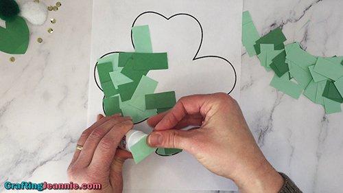 adding green scraps of paper to shamrock