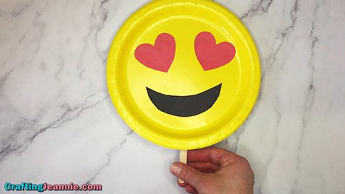 holding heart emoji plate by popsicle stick