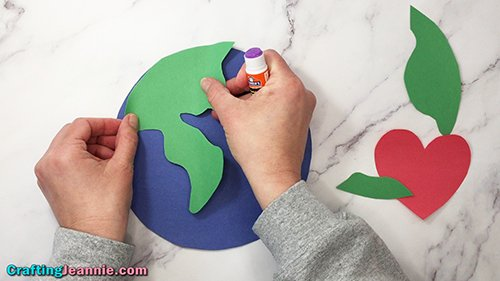 gluing green land onto earth day craft - Crafting Jeannie