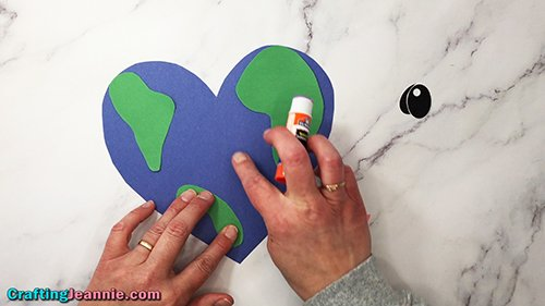 gluing last of green land onto blue heart earth