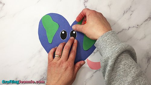 gluing eyes onto blue heart earth