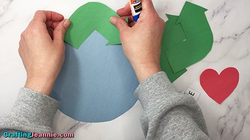 gluing arrow on recycling craft