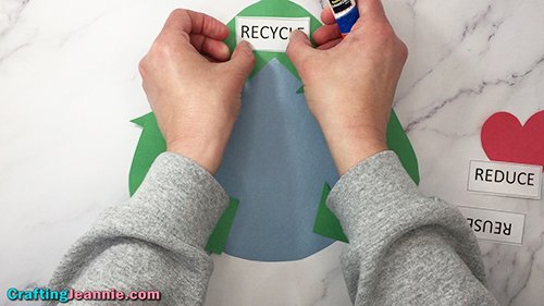 gluing on word recycling for earth day craft