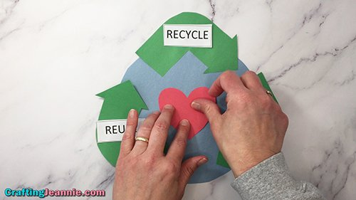gluing on heart of recycle craft