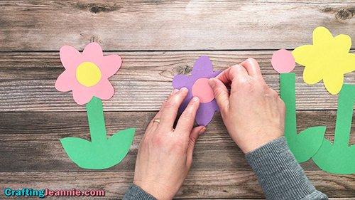 Daisy Craft - gluing center onto paper flower for preschoolers