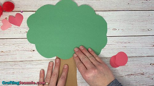 Gluing the trunk onto the apple tree craft