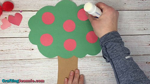 Gluing the apples onto the apple tree craft