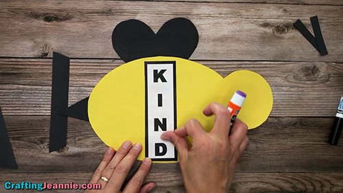 Gluing Kind words onto bee craft