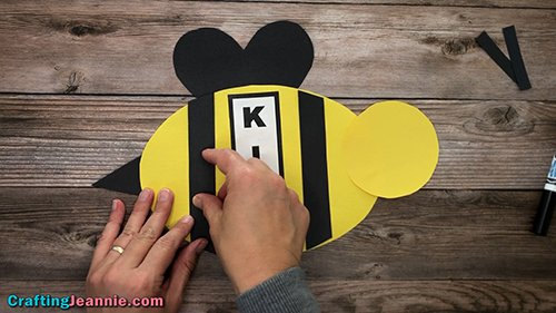 gluing back stripe onto kindergarten bee craft