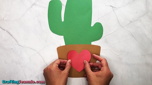 gluing the heart onto the paper cactus pot