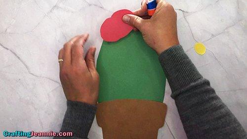 glue the red flower onto the preschool cactus craft