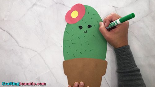 drawing a face onto the paper cactus
