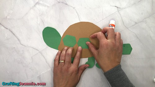 Gluing decorations onto the turtle craft shell