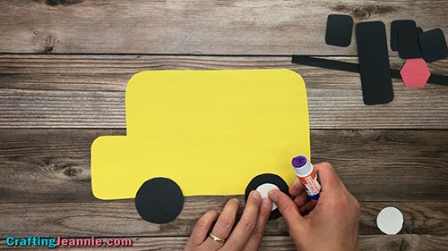 gluing hubcabs onto the school bus craft wheels