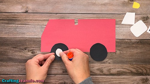 gluing hubcaps onto the Fire Truck craft wheels